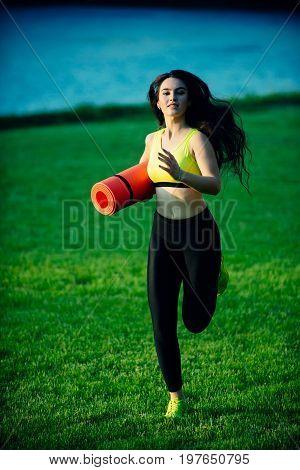Woman Running On Green Grass.