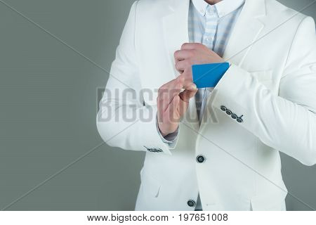 Empty business card in cuff. Businessman in white jacket on grey background. Ace up sleeve concept. Advantage and secret trump. Cheating and trick