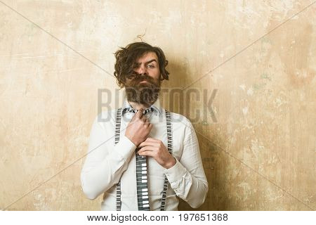 Guy or businessman at textured wall. Fashion model with stylish hair. Business fashion and beauty. Man with long beard and mustache on serious face. Hipster in shirt and suspenders with musical tie.