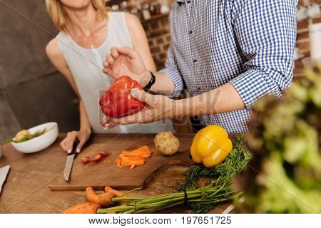 Making salad. Wonderful witty energetic people using fresh vegetables while making a meal at home and choosing the ingredients