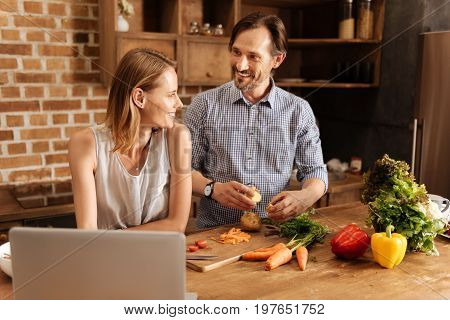 Managing the cooking. Amazing emotional lovely couple spending their weekend at home and cooking dinner together while finding the recipe online
