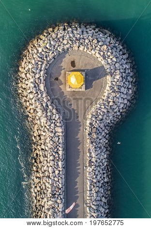 Aerial image of a lighthouse with people fishing