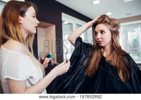 Hair stylist working on female customer s hairdo clipping strands with hair pins in hairdressing studio.