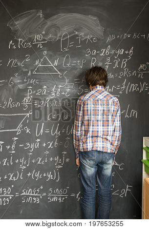 Teenageer Boy, standing near blackboard and having trouble with complicated math formulas