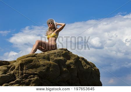 Young Girl Sitting On The Rock Tanning