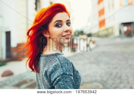 Startled Young Redhead Woman Looking Back Over Her Shoulder At The Camera As She Strolls Down A Dese