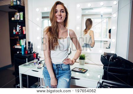 Portrait of young smiling female model with long fair hair wearing casual clothes standing in make-up studio against makeup table and mirrors.