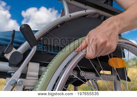 Handicapped Disabled Man Sitting On Wheelchair Outdoors In Meado