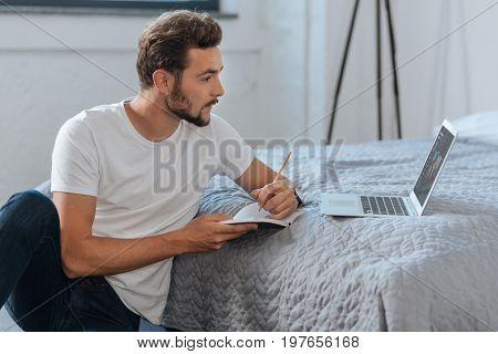 Make notes. Attentive male person sitting in semi position and putting elbow on the bed while looking at laptop