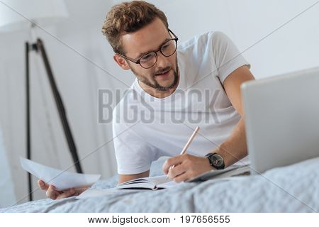 Not to forget. Attractive male person keeping smile on his face and looking at computer while working at home