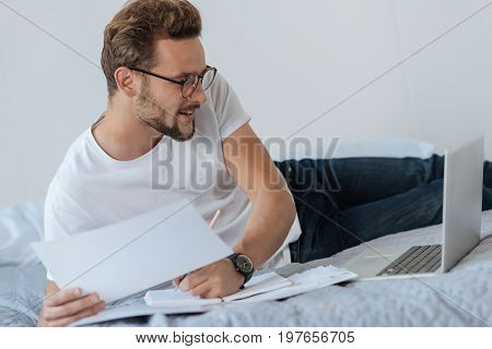 Smile and do. Handsome man keeping smile on his face and holding pen in left hand while looking at laptop