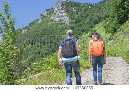 Travelers travel on the road in mountains go trekking together. Trekking together. Travel adventure and hiking activity active and healthy lifestyle on summer vacation and weekend tour