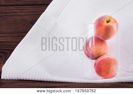 Three big and whole peaches in a transparent glass on a light fabric and on a dark brown wooden background. Appetizing peaches full of vitamins. Vegetarian lifestyle. Summer fruits.