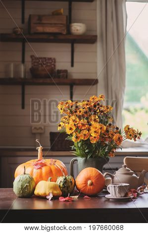 fresh assorted pumpkins and squash on the table at country house with seasonal autumn flowers for thanksgiving