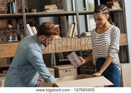 Collecting things. Young female leaning on box while holding glass vase in right hand and showing it to her man
