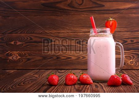Close-up of a mason jar with strawberry smoothie on the wooden background. A few strawberries are near a full jar of strawberry milkshake with pink straw and decorative strawberry. Healthy drinks.