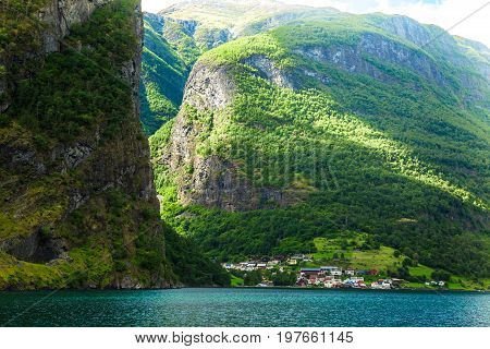 Small village with a lovely backdrop at Flam Fjords, Norway. Mountains and fjord in Norway. Clouds and blue sky. Beautiful stunning views of mountains, water, sky, clouds and sun. Norwegian nature