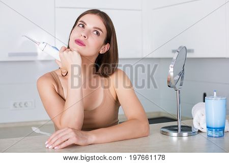 Woman With Toothbrush And Oral Irrigator