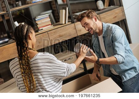 Want to take it. Handsome male person keeping smile on his face and standing opposite his girlfriend while putting things into box