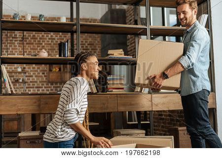 Put it somewhere. Handsome male person keeping smile on his face and holding big box while standing in semi position in front of his girl