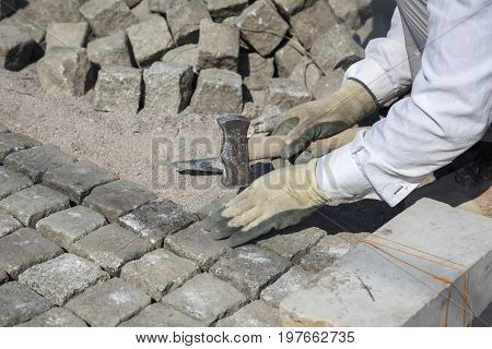 Worker installing granite cubes for pathway. Laying natural granite stone cobbles in sand. Natural stone paving. Shallow DOF.