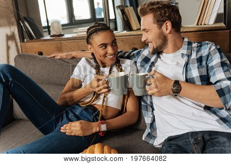 Enjoying new apartments. International young woman having many braids on her head and holding big cup while looking into eyes of her man