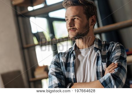 Flying in thoughts. Attractive bearded male person keeping smile on his face and crossing arms on chest while looking aside