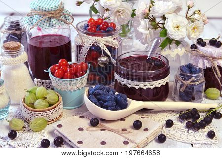 Spoon and vintage jars with homemade jam and fresh berry. Making fruit jam concept. Fresh berry on wooden table, summer still life and rustic food vintage background. Preserved fruits