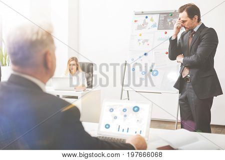 Inefficient negotiations. Tired stressed intelligent man looking disappointed talking to his colleague and explaining him the strategy while he not getting the general idea