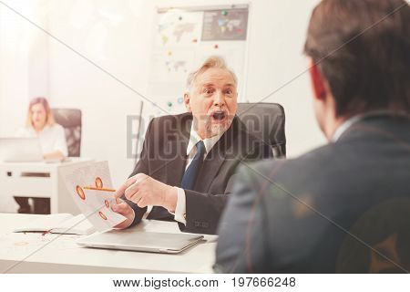 Emotional breakdown. Expressive distressed aggressive man fining a huge mistake in the report his colleague making and pointing it out emotionally