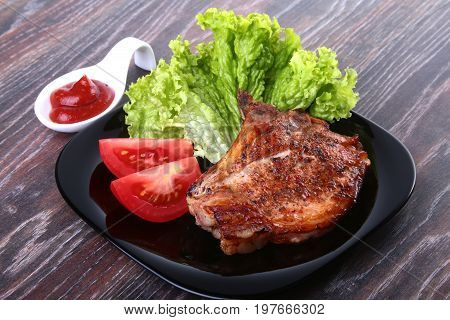 grilled pork chops with tomato, leaves lettuce and ketchup on plate