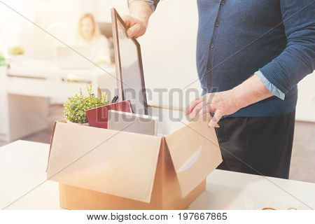 Personal items. Prepared weary sad employee storing his belongings in a box as leaving his workplace while being fired