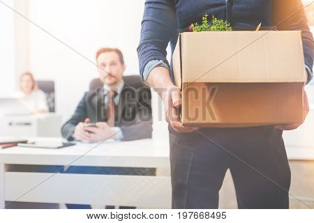 Leaving career behind. Tired upset professional gentleman holding a box with the belongings he taking with him as he walking out of the office