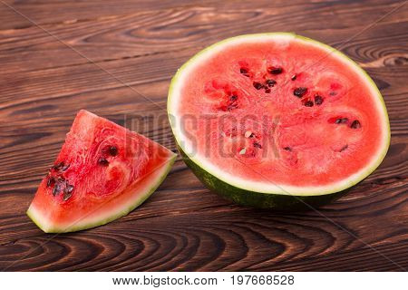 A slice and a half of a summer juicy watermelon. Watermelon is cut showing a hard, green rind,  sweet watery reddish flesh, and black tiny seeds. Refreshing taste of hot summer brings bliss.