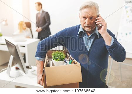 Hear me out. Attentive serious troubled gentleman calling his wife and telling her he quitting the job while holding his belongings a box