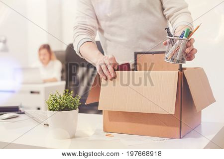 Nothing left behind. Attentive dedicated fired man packing his stuff in a box as he cleaning his workplace before leaving the office