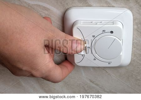 Under floor heating thermostat close-up of a hand pressing a button.