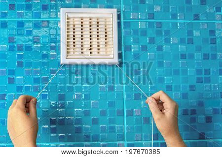 Wall ventilation grille air flow regulator with cord hands pull the ropes adjusting the shutters.