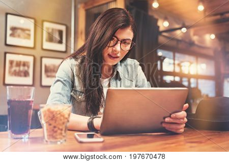 Positive emotions. Enigmatical female person using her computer while being in pub and waiting her friends