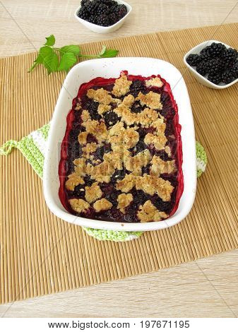 Homemade blackberry crumble in baking form and fresh blackberries