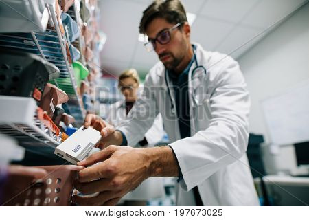 Pharmacist looking for a drug on shelf. Male pharmacist checking stock in an shelf. Medical staff working in hospital pharmacy.
