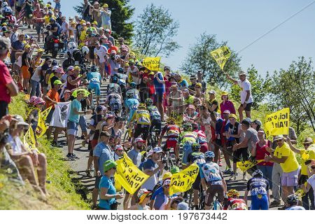 Col du Grand ColombierFrance - July 17 2016: The peloton with Froome in Yellow Jersey riding on the road to Col du Grand Colombier in Jura Mountains during the stage 15 of Tour de France 2016.