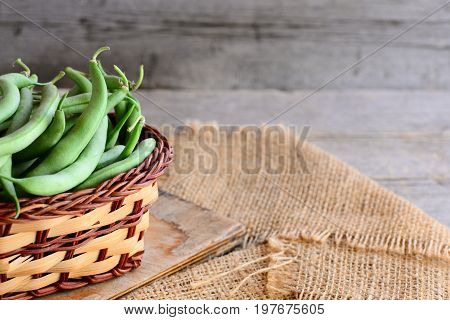Green string beans in a brown basket and on a burlap textile. Natural young beans pods. Old wooden background with empty space for text. Green string beans crop concept