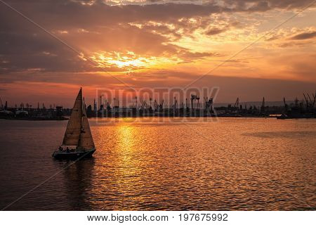 Sailing Yacht Enters The Harbor At The Sunset