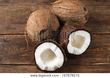Close up of coconuts on old wooden background. Tropical nut with fresh white pulp and hard shell