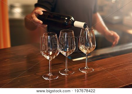 Sommelier pours pinot gris wine in glasses for degustation