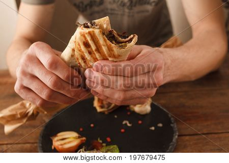 Man eating shawarma on big plate. Grilled lavash with meat and herbs, close up picture. Customer in restaurant