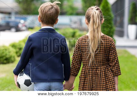 Back View Of Two Adorable Schoolchildren Holding Hands While Walking Together After School