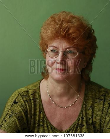 Portrait of a middle-aged red-haired woman wearing glasses and a green dress with chain on the neck with a serious look and turn your head for 3/4 on a light green background