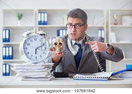 Businessman smoking holding human skull and an alarm clock in th